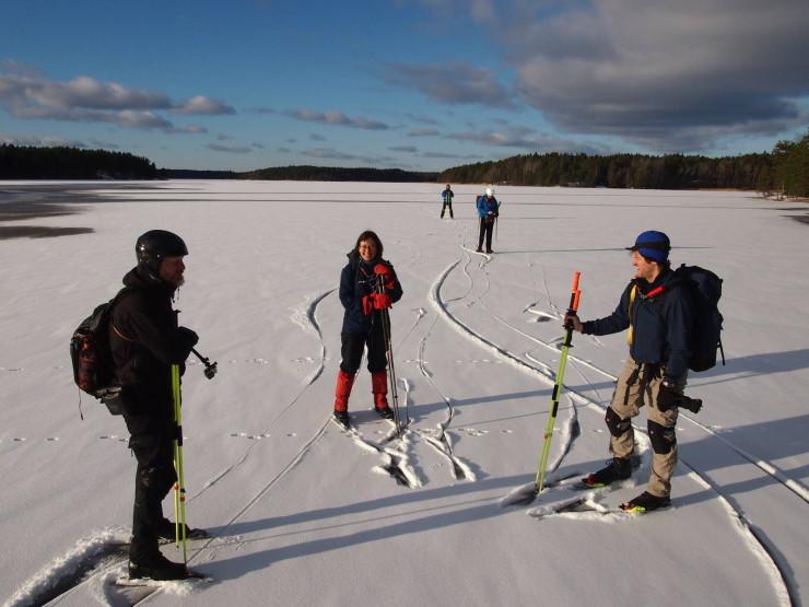 Bilde viser tre skøyteløpere som treffes på isen og utveksler erfaringer.