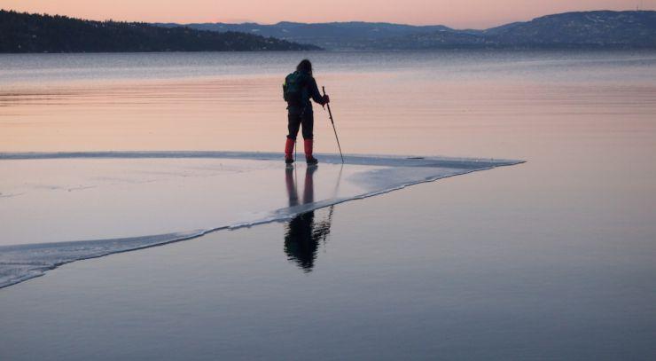 Bildet viser en skøyteløper som har dristet seg helt ut til iskanten mot åpent vann.