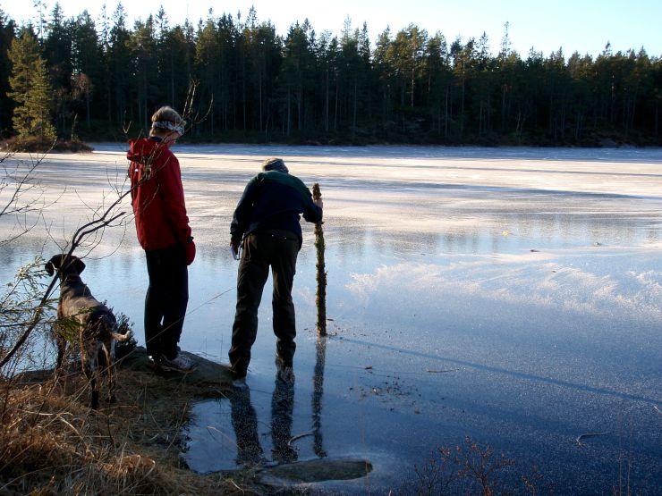 Bildet viser personer som slår en trestokk i isen for å sjekke istykkelsen.