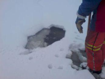 Bildet viser et åthull som delvis er skjult under snøen.