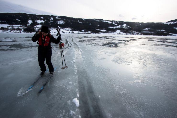 Bildet viser en skiløper på et vann hvor det er så mye overvann at sørpen nesten går over skiskoene.