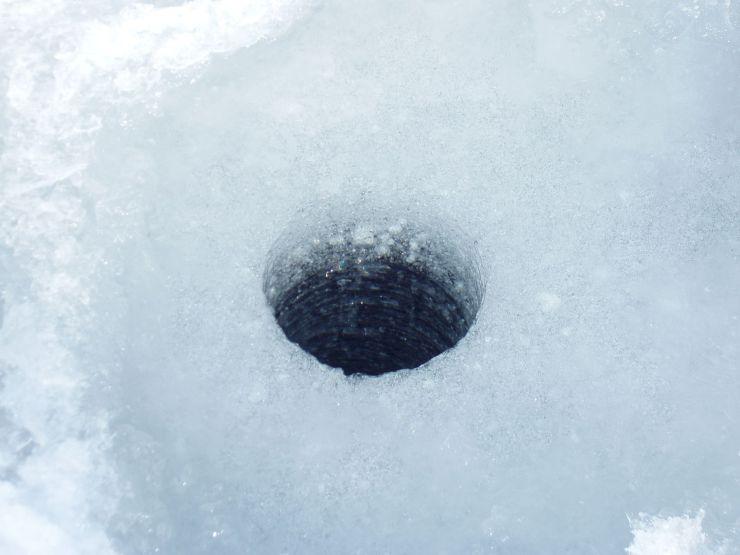 Bildet viser et borehull der man tydelig se at det er lys sørpeis over mørk stålis.