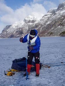 Bildet viser en som borer seg gjennom isen på Gjende med et isbor.