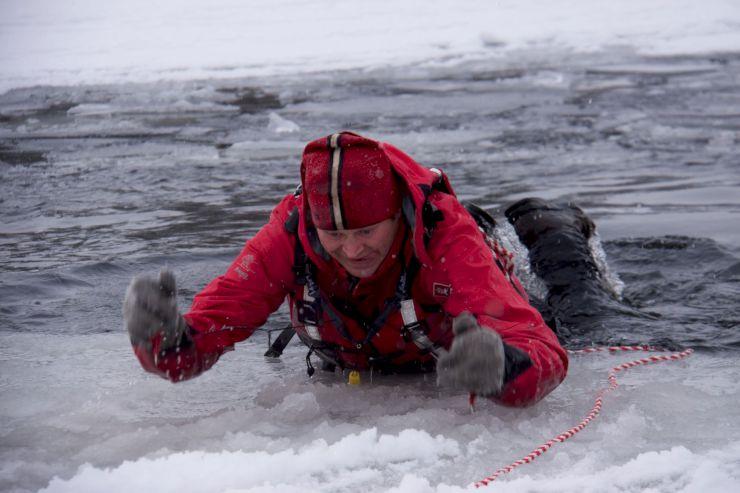 Bildet viser en som drar seg opp på isen ved hjelp av ispigger.