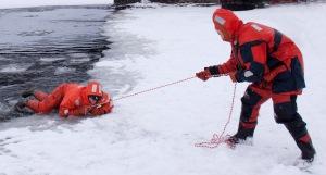 Bildet viser en som dras inn på isen med en kasteline.