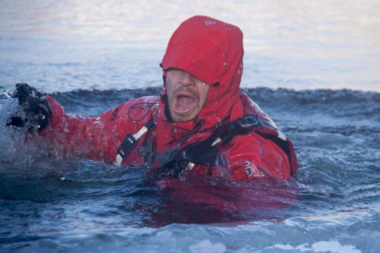 Bildet viser en som har falt i vannet med redningsvest på.
