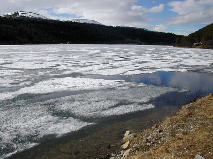Bildet viser et vann i vårløsningen hvor isen har løsnet fra land.